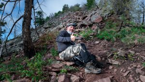 Dave Spates gives a thumbs up, right below Bear Peak, wearing a goPro headmount