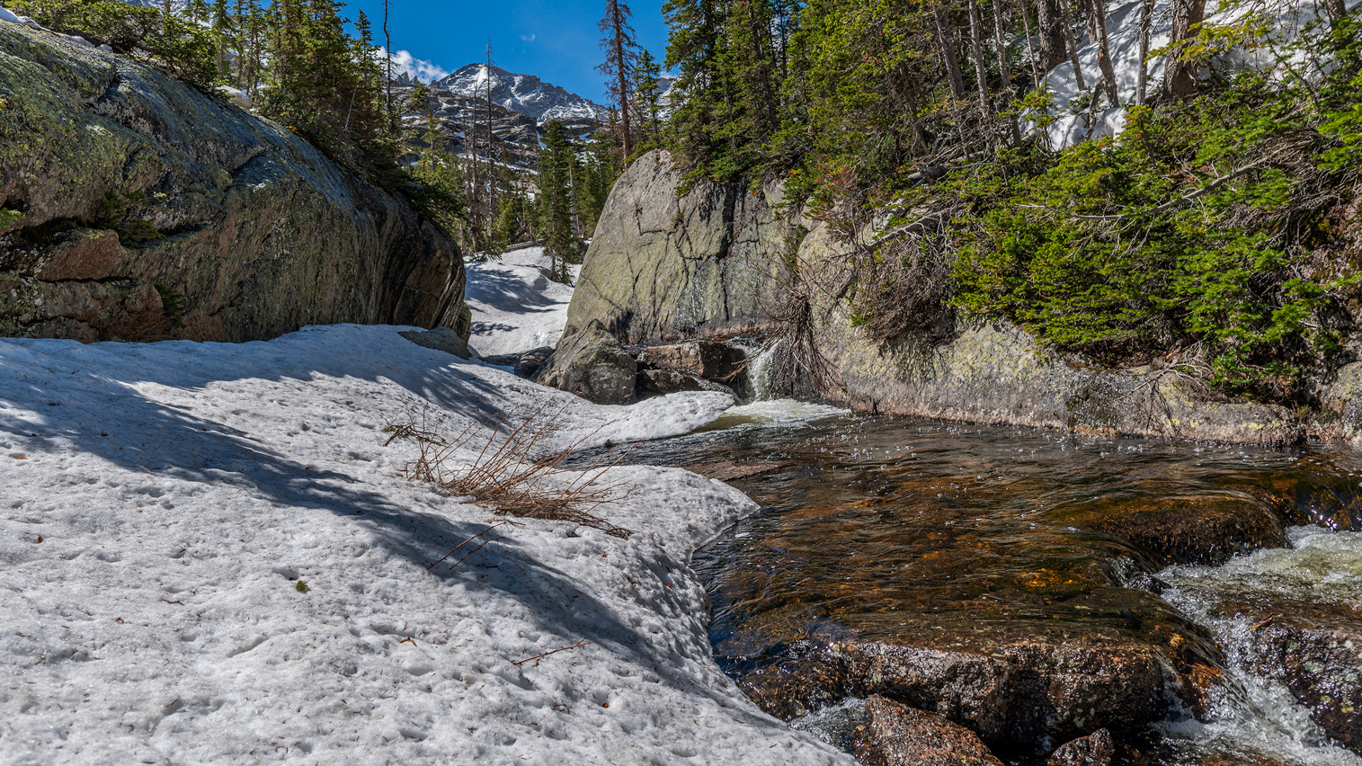 Snow covered Glacier Creek in Spring time Rocky Mountain National Park