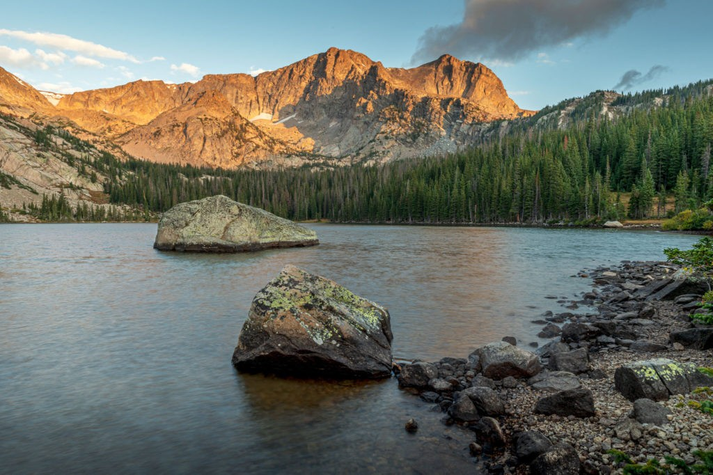 Sunrise at Thunder Lake, from the shore, rocks, lake surrounded by trees, Mt Alice in the background